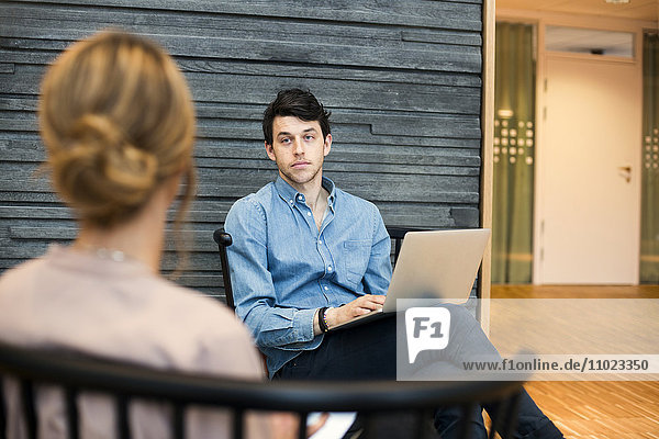 Businessman looking at businesswoman during meeting at hotel lobby