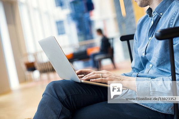 Midsection of businessman using laptop at hotel lobby