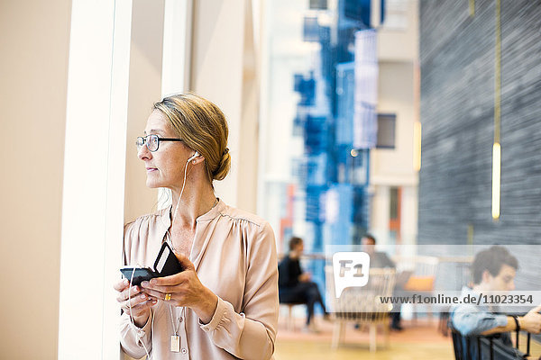 Businesswoman looking through window while listening music on smart phone at hotel lobby