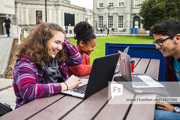 Smiling university students with laptops on table at campus
