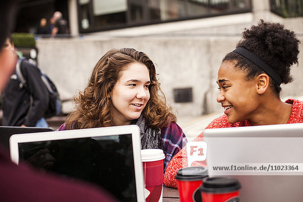 Young female friends talking at university campus