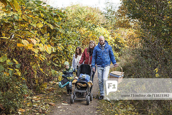 Full length of parents with children walking on footpath amidst trees during autumn