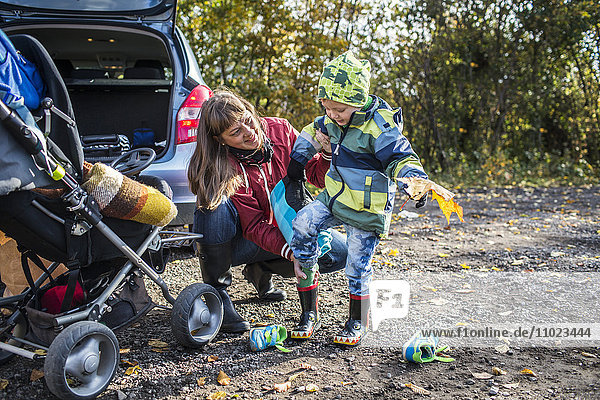Mature mother assisting boy in wearing rubber boot during picnic