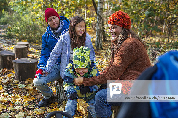 Happy family of four spending leisure time in forest