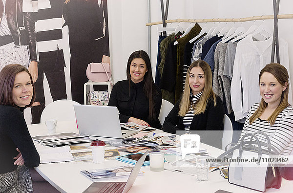 Portrait smiling fashion buyers meeting in messy office