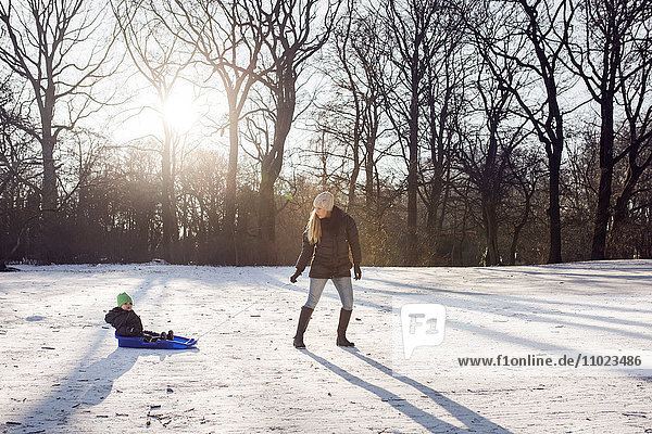Full length of young woman pulling baby boy on sled