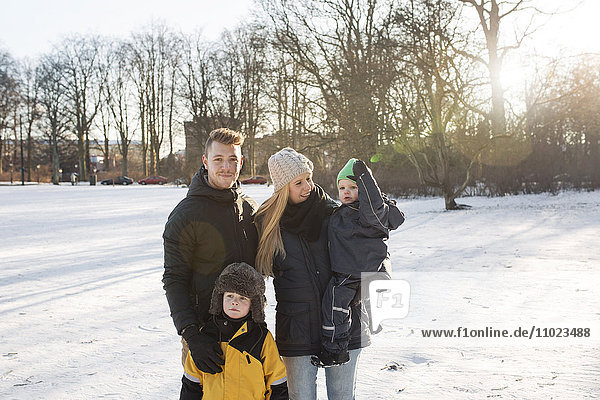 Portrait of young man with family standing on snow covered field