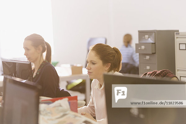 Focused businesswomen working at computers in office