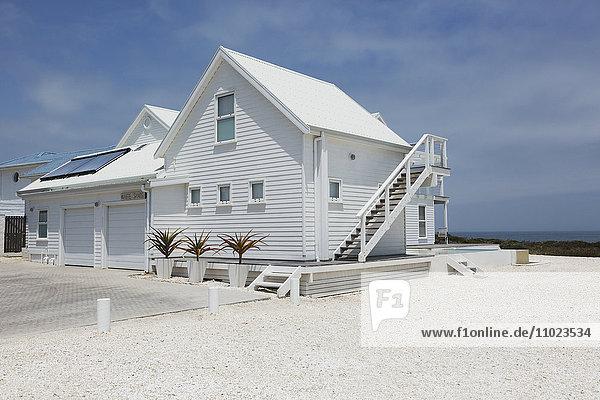 White beach house under sunny blue sky