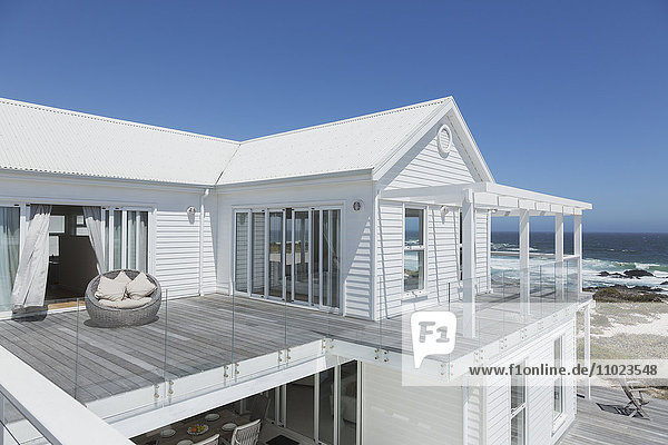 White beach house with balcony with ocean view under sunny blue sky