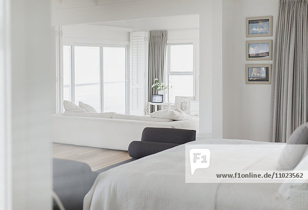 White bedroom open to living room in home showcase
