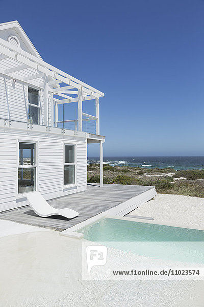 White beach house and swimming pool with ocean view under sunny blue sky