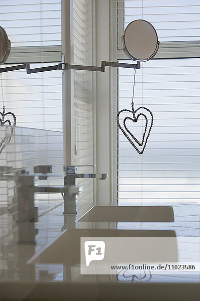 Heart-shape decoration hanging from mirror in home showcase bathroom