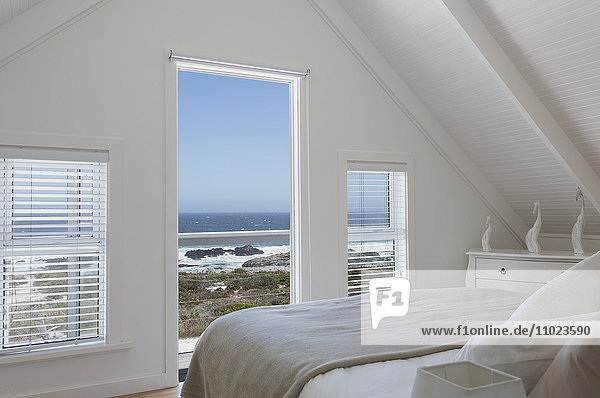 Vaulted ceiling in white home showcase bedroom with sunny ocean view
