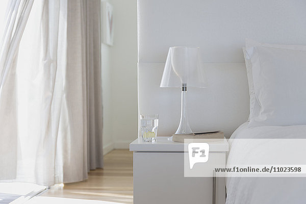 White lamp and bedside table in home showcase bedroom