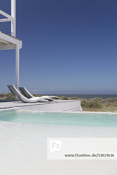 Modern lounge chairs at poolside with ocean view under sunny blue sky
