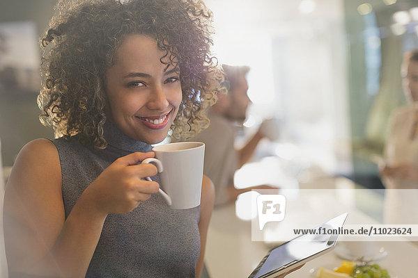 Portrait smiling businesswoman drinking coffee using digital tablet