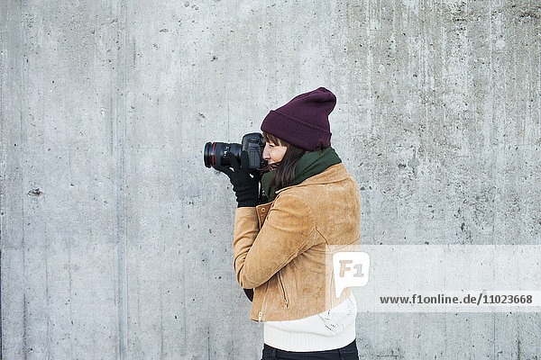 Woman wearing jacket photographing against wall