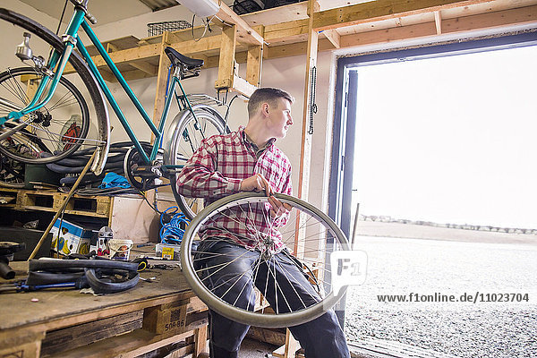 Repairman looking away while holding bicycle tire in workshop