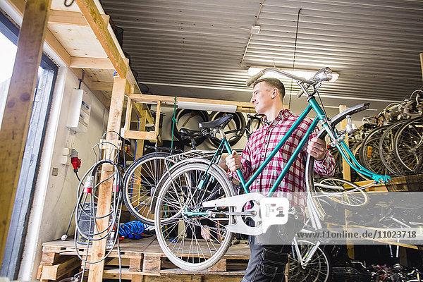 Repairman looking away while carrying bicycle in workshop