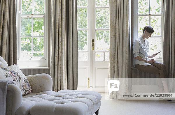 Woman using digital tablet at window in bedroom