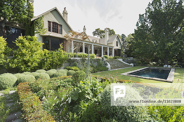 Home showcase exterior with swimming pool and lush garden