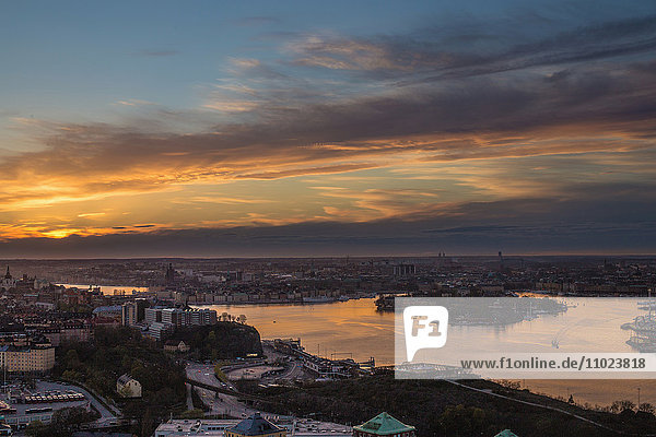 Scenic view of lake and residential district against cloudy sky during sunset