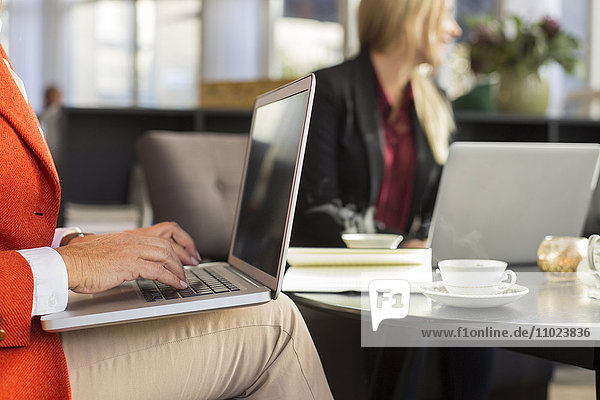 Midsection of businesswoman using laptop in meeting at restaurant