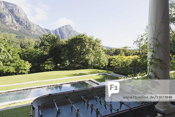 Foosball table on luxury patio overlooking swimming pool and mountain
