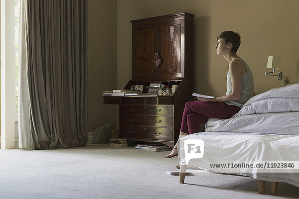 Pensive woman reading letter on bed