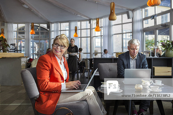 Male and female business colleague using laptops in restaurant