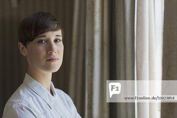 Portrait confident brunette woman at window