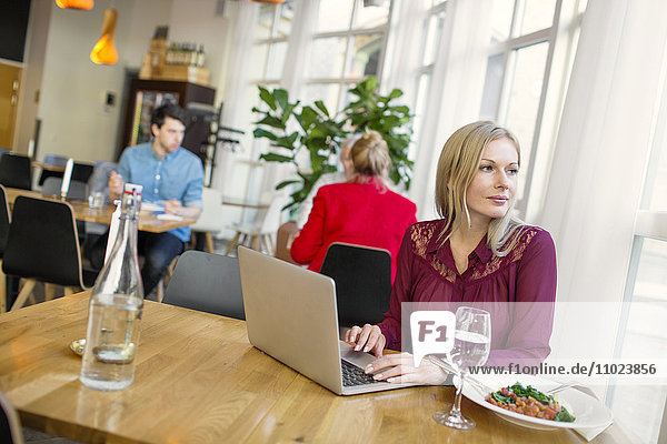 Businesswoman looking away while using laptop in restaurant