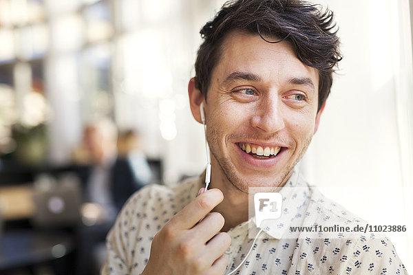 Man smiling while talking through earphones at restaurant