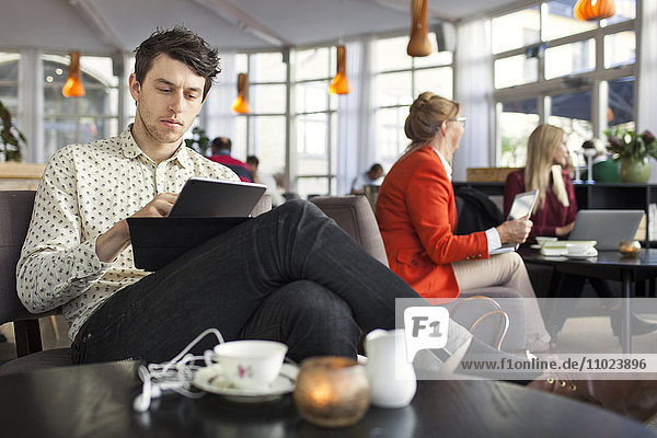 Businessman using digital tablet while colleagues working in background