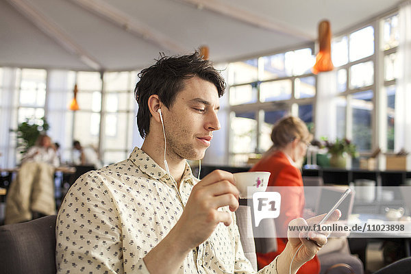 Man having coffee while using mobile phone in restaurant
