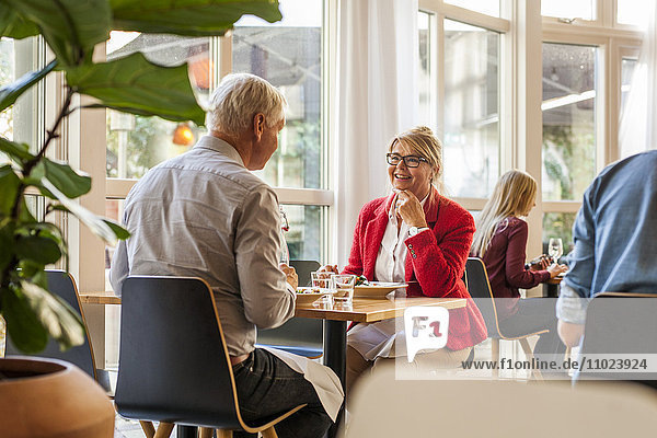 Senior business people discussing while having lunch in restaurant