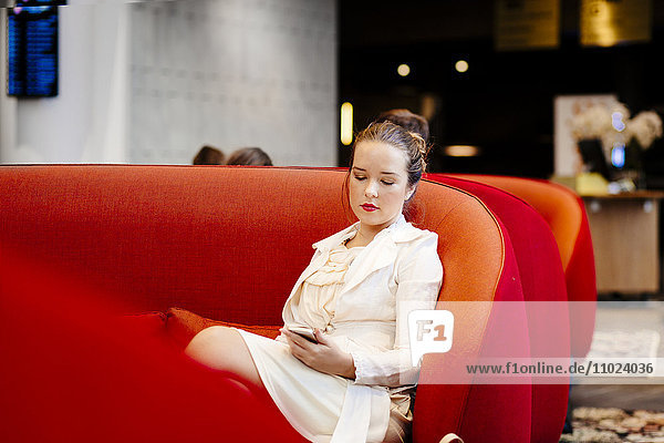 Businesswoman holding smart phone while sitting on red sofa at hotel