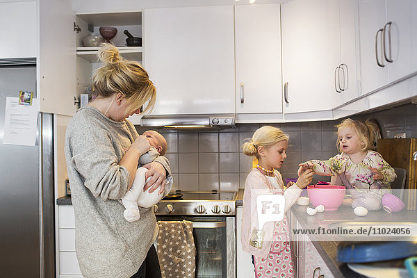 Mother carrying baby while sisters preparing pancake in kitchen