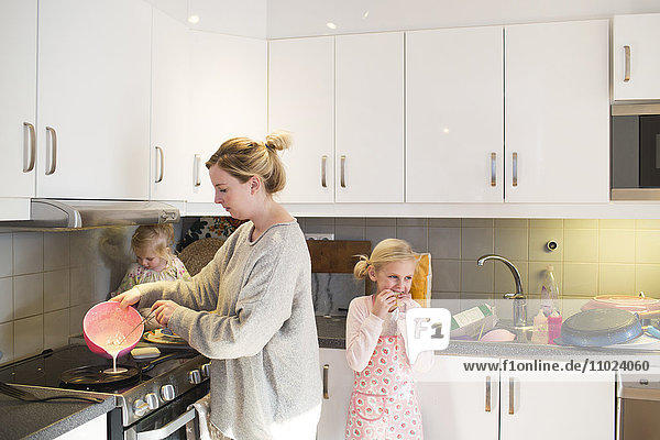 Mother preparing pancake on stove in kitchen
