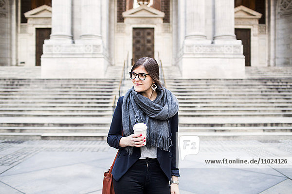 Confident businesswoman holding coffee cup standing in front of New York Public Library