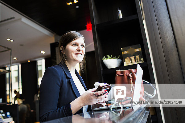Smiling businesswoman with smartphone and laptop at coffee shop