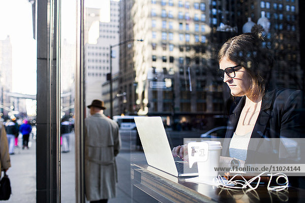 Businesswoman using laptop while sitting at coffee shop seen through window