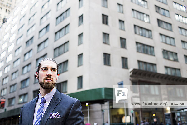 Low angle view of businessman standing against buildings in city