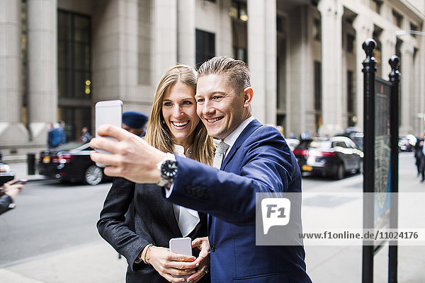 Smiling businessman and woman taking selfie while standing at city