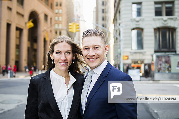 Portrait of smiling businessman and woman standing on city street