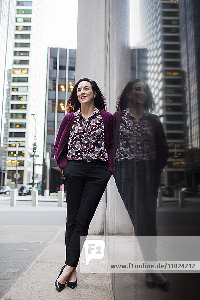 Confident businesswoman standing on sidewalk by glass window