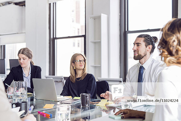 Businessman discussing with colleagues at conference table during meeting