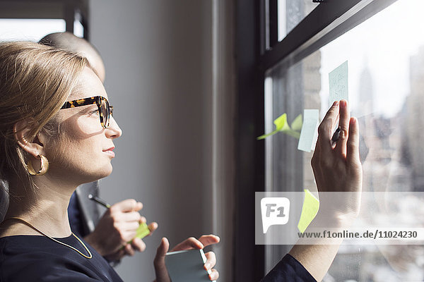 Side view of businesswoman sticking notes on glass window at office