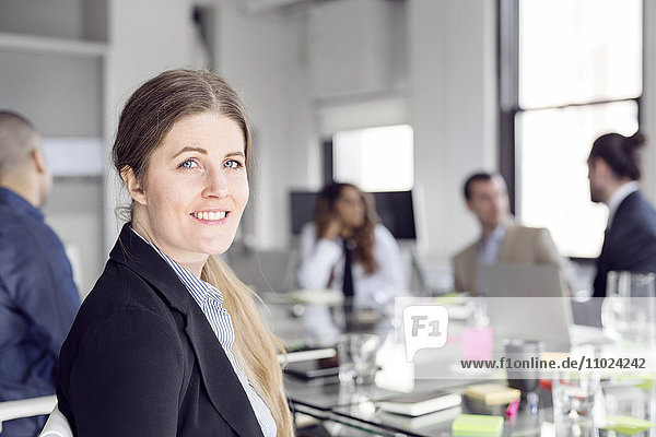 Close-up of smiling businesswoman sitting with colleagues at conference table